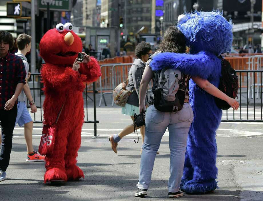 An Elmo character, left, uses a woman's camera to photographer her with a Cookie Monster character, in New York's Times Square, Tuesday, April 9, 2013.  A string of arrests in the last few months has brought unwelcome attention to the growing number of people, mostly poor immigrants, who make a living by donning character outfits, roaming Times Square and charging tourists a few dollars to pose with them in photos. Photo: Richard Drew, AP / AP