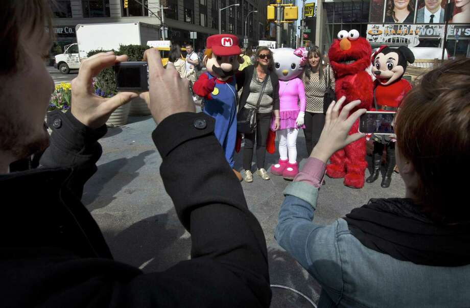 People have their photos taken with Super Mario, Hello Kitty, Elmo and Minnie Mouse characters in New York's Times Square, Tuesday, April 9, 2013.  A string of arrests in the last few months has brought unwelcome attention to the growing number of people, mostly poor immigrants, who make a living by donning character outfits, roaming Times Square and charging tourists a few dollars to pose with them in photos. Photo: Richard Drew, AP / AP