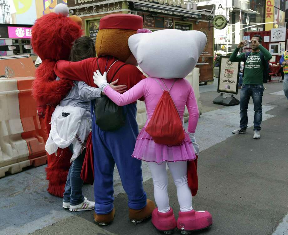 Elmo, Super Mario, and Hello Kitty characters pose for photo, in New York's Times Square, Tuesday, April 9, 2013.  A string of arrests in the last few months has brought unwelcome attention to the growing number of people, mostly poor immigrants, who make a living by donning character outfits, roaming Times Square and charging tourists a few dollars to pose with them in photos. Photo: Richard Drew, AP / AP