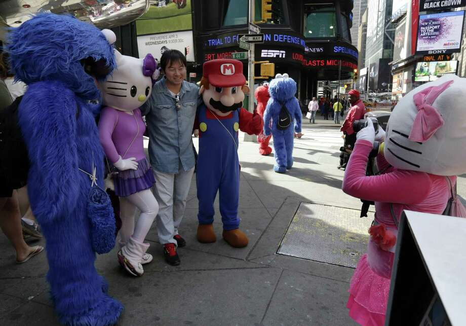 A man is has his photo taken by a Hello Kitty character, right, as he poses with Cookie Monster, another Hello Kitty and Super Mario characters, in New York's Times Square,  Tuesday, April 9, 2013.  A string of arrests in the last few months has brought unwelcome attention to the growing number of people, mostly poor immigrants, who make a living by donning character outfits, roaming Times Square and charging tourists a few dollars to pose with them in photos. Photo: Richard Drew, AP / AP