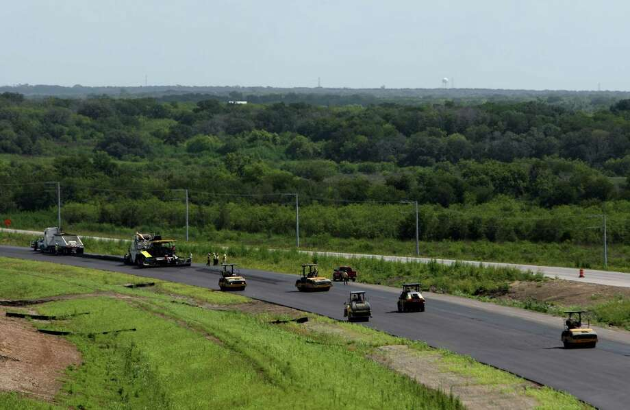 Workers pave sections of Texas 130, the state's first public-private toll road, in 2012. A reader suggests a more cost-efficient solution to help San Antonio save money on paving the roads. Photo: File Photo, San Antonio Express-News / ¨2012 HELEN MONTOYA PHOTOGRAPHY