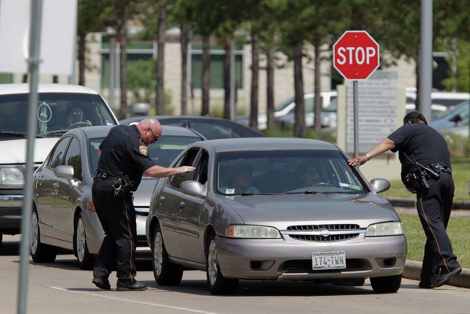 Harris County Sheriff's Deputies check vehicles leaving Lone Star College's Cypress-Fairbanks campus. Photo: James Nielsen, Houston Chronicle / © 2013 Houston Chronicle
