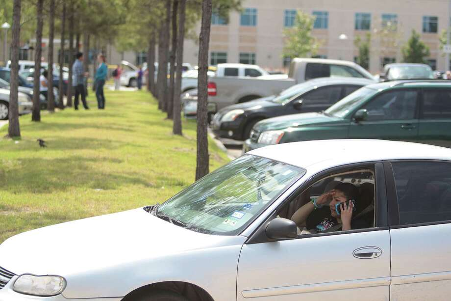 Students wait to exit a parking lot as police search vehicles as they leave the Cy-Fair campus of Lone Star College after 14 people were wounded in a stabbing. Photo: Mayra Beltran, Houston Chronicle / © 2013 Houston Chronicle