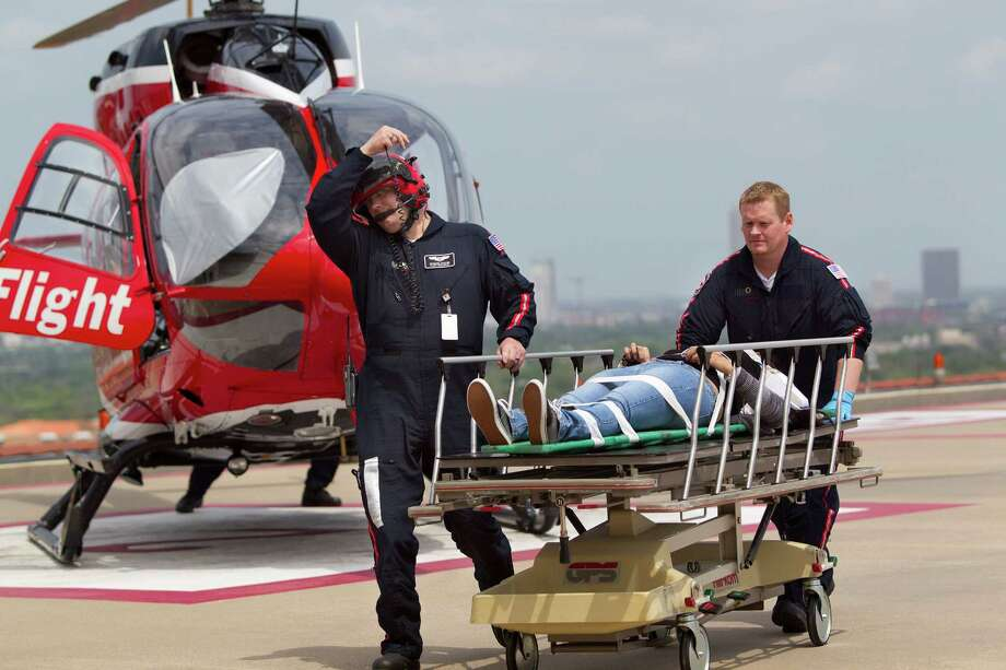 Life Flight crew members escort one of the at least 12 people who were stabbed by a person at Lone Star College Cy-Fair campus and were flown by Memorial Hermann Life Flight to Memorial Hermann Hospital in the Texas Medical Center Tuesday, April 9, 2013, in Houston. Photo: Johnny Hanson, Houston Chronicle / © 2013  Houston Chronicle