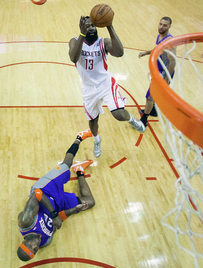 Rockets guard James Harden leaps over Phoenix center Jermaine O'Neal as he goes up for a basket. Photo: Smiley N. Pool, Houston Chronicle / © 2013  Houston Chronicle
