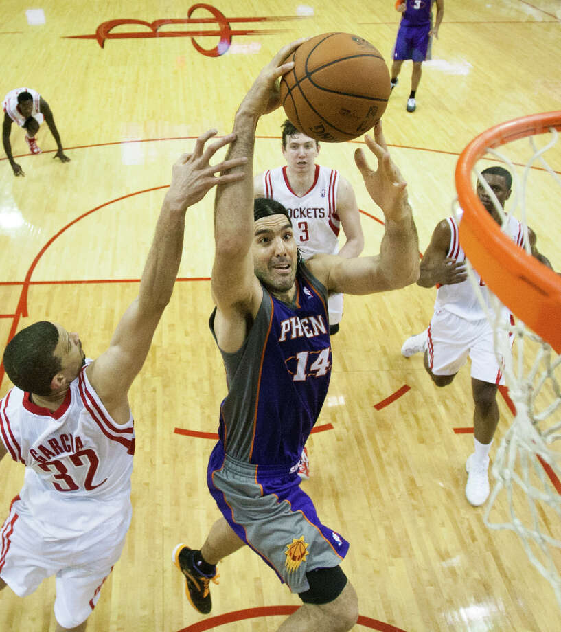 Suns power forward Luis Scola  goes up for a shot past Rockets guard Francisco Garcia.  Scola scored 28 points in the game. Photo: Smiley N. Pool, Houston Chronicle / © 2013  Houston Chronicle