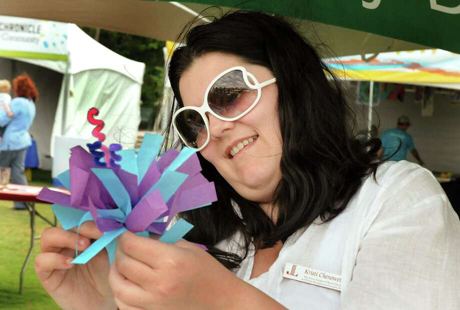 Rosemary Hickman, of Spring, makes a paper flower for a child during the 7th Annual Woodlands Waterway Arts Festival along The Woodlands Waterway and in Town Green Park. The Festival features 200 juried fine art and fine craft artists from 36 different states and 3 countries, plus local arts and crafts booths for children. Photo by David Hopper Photo: David Hopper, Freelance / freelance