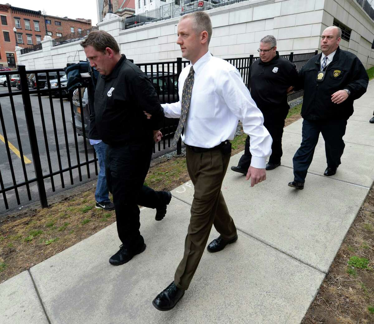Albany County corrections officers Timothy Robillard, 44, left, and James Cerniglia, 47, right, both of Clifton Park, are escorted into the Albany County Judicial Center Wednesday, April 10, 2013. The officers are accused of running a Capital Region bookmaking ring in which bets and payoffs were routinely taking place at the jail. (Skip Dickstein/Times Union)