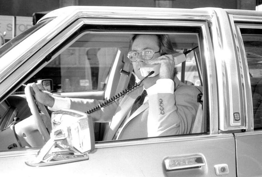 Nov. 23, 1990: Note how this San Francisco driver uses his left ear, just so everyone can see his awesome high-tech car phone. I like to imagine Gordon Gekko is on the other line, standing on a beach screaming something about Bluestar Airline. / ONLINE_YES
