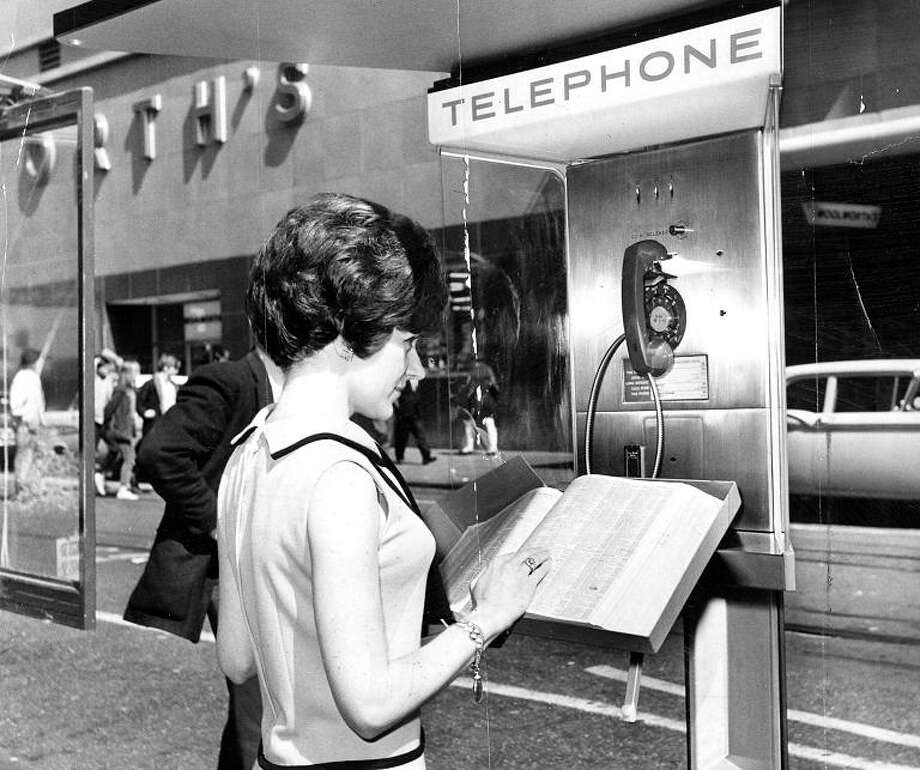 March 7, 1967: Gail Anglim works a new pay phone on the corner of Eddy and Powell in SF. Note the space-age design ... and the rotary dialer. Photo: Stan Creighton, The Chronicle / ONLINE_YES