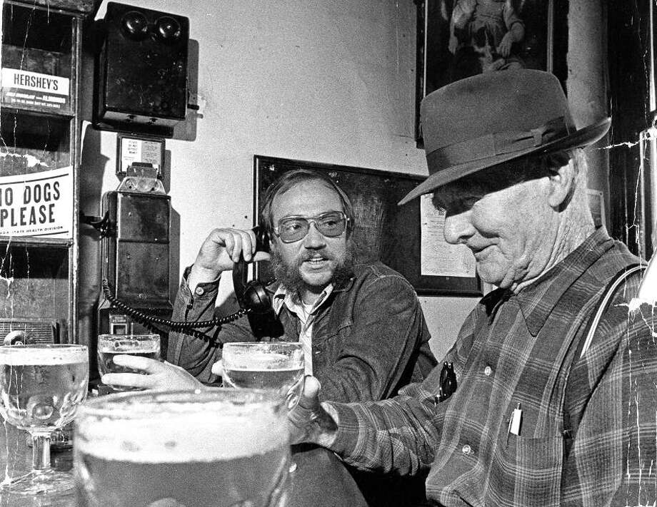 May. 24, 1972: Johnny Gunn and Richard Bauman use the magnetic crank box on top of an old telephone at the Silver Queen Saloon. I\'m betting the phone is gone, but I\'m hoping both of these guys are still there. Photo: Vincent Maggiora, The Chronicle / ONLINE_YES