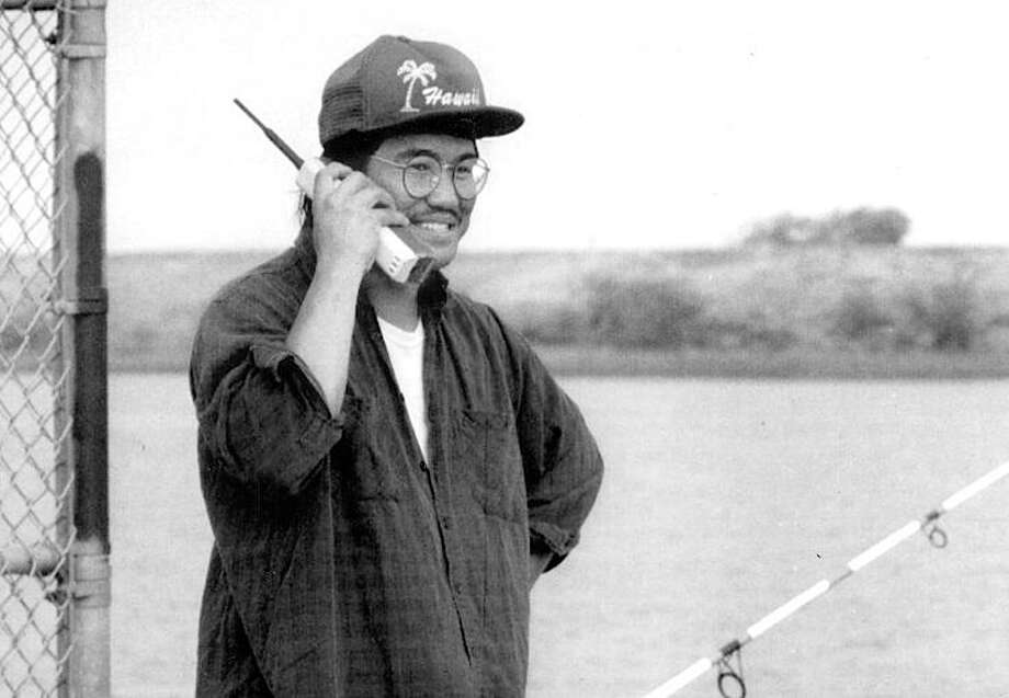 Oct. 24, 1992: Ray Basa makes a call on his sweet cell phone while fishing near Antioch. I love the Hawaii hat. Basa is No. 2 behind Ms. Love on my list of people in this  gallery I\'d most like to party with. Photo: Deanne Fitzmaurice, The Chronicle / ONLINE_YES