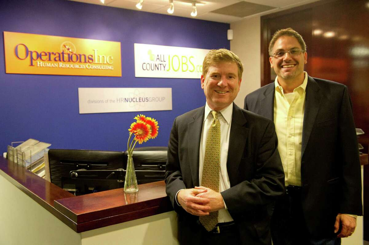 Davbid Lewis, President and CEO of OperationsInc., left, and John Hannigan of Choyce Peterson, right, pose for a photo in the lobby of OperationsInc.'s Norwalk office on Wednesday, April 10, 2013.