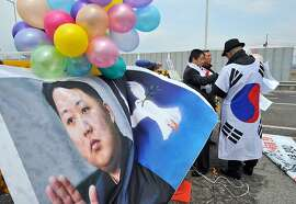 "TOPSHOTS South Korean activists set balloons on a banner showing pictures of North Korean leader Kim Jong-Un (L) and a dove of peace (C) during a rally urging regular operations of the Kaesong joint industrial complex on the road leading to North Korea at a military checkpoint in the border city of Paju on April 10, 2013. The banner reads ""We want National Defence Commission chairman Kim Jong-Un to put the Kaesong industrial complex back into operation immediately and stop nuclear and missile test launches for national peace"". South Korean and US forces raised their alert status to ""vital threat"" on April 10, ahead of an expected North Korean missile test, with tensions wound tight during a five-day buildup to a key anniversary.  AFP PHOTO / JUNG YEON-JEJUNG YEON-JE/AFP/Getty Images"
