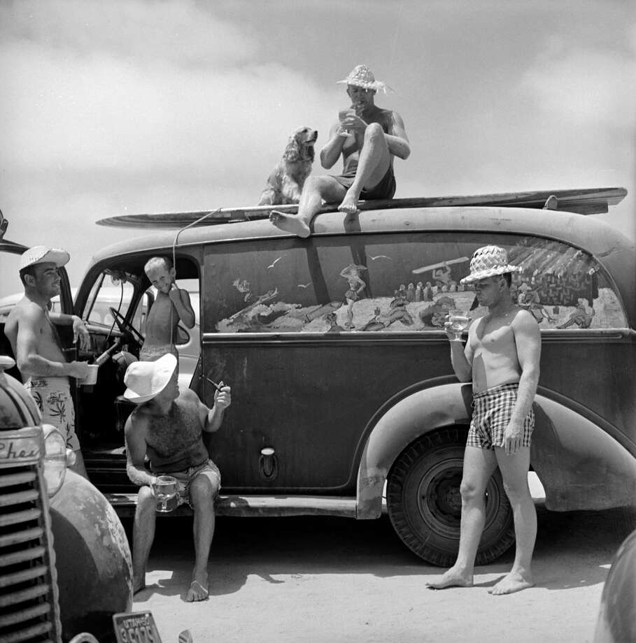 "American surfer Bob ""Hammerhead"" Gravage sits on top of his van with his dog, Cork McNork, as he hang out on the beach with friends, San Onofre, California, July 1950. Photo: Loomis Dean, File / Time & Life Pictures"
