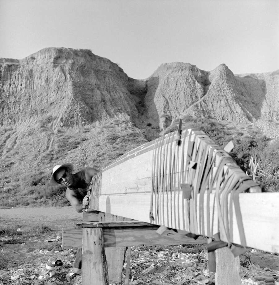 An unidentified surfer begins assembly of the roof of a thatched hut he and others intend to build on the beach, San Onofre, California, July 1950. Photo: Loomis Dean, File / Time & Life Pictures