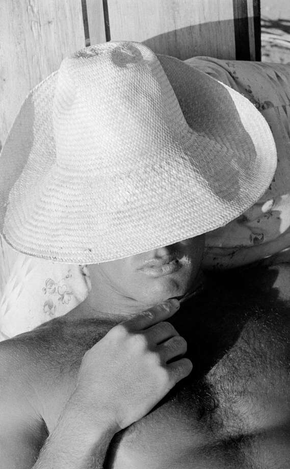Close-up of an unidentified surfer whose face is hidden by an over sized hat as he relaxes on the beach, San Onofre, California, July 1950. Photo: Loomis Dean, File / Time & Life Pictures
