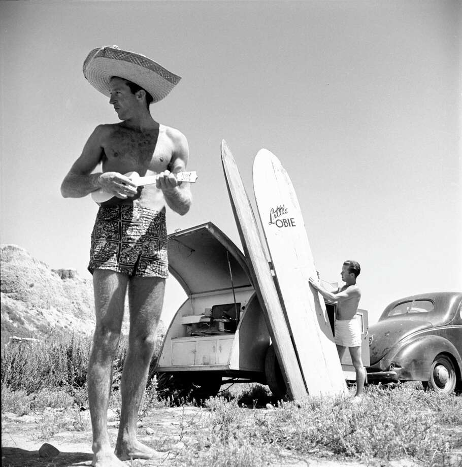 An unidentified surfer plays a ukulele and wears a large straw hat as he stands nears parked cars where another surfer readies several surfboards on the beach, San Onofre, California, July 1950. Photo: Loomis Dean, File / Time & Life Pictures