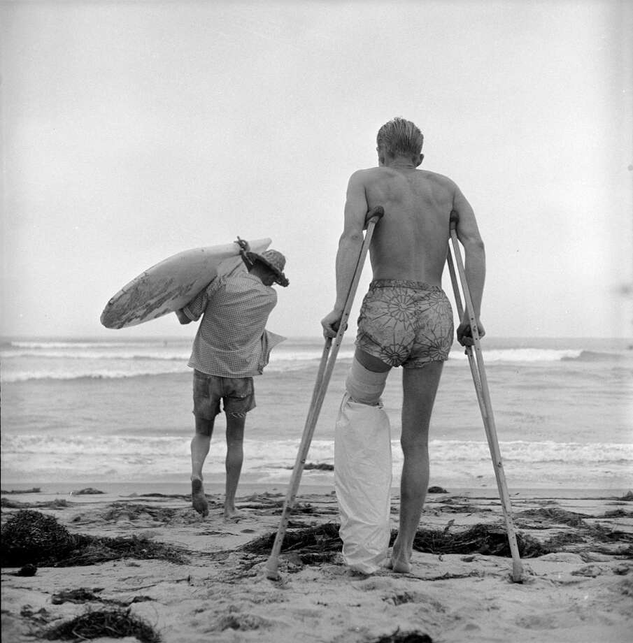 American surfer Jim Elliot uses crutches to walk out to the water as a friend holds his surfboard on the beach, San Onofre, California, July 1950. Elliot has a plastic bags tied around his cast so he can still surf. Photo: Loomis Dean, File / Time & Life Pictures