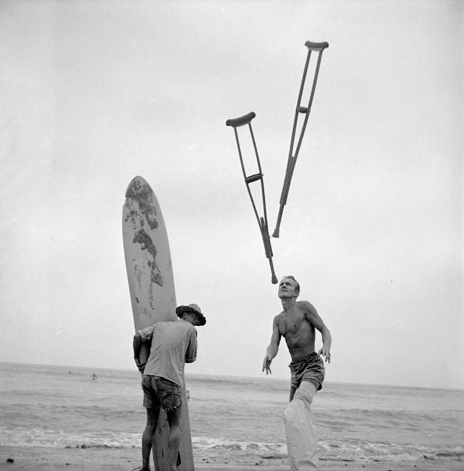 American surfer Jim Elliot throws his crutches back onto the beach while a friend holds his surfboard, San Onofre, California, July 1950. Elliot has a plastic bags tied around his cast so he can still surf. Photo: Loomis Dean, File / Time & Life Pictures