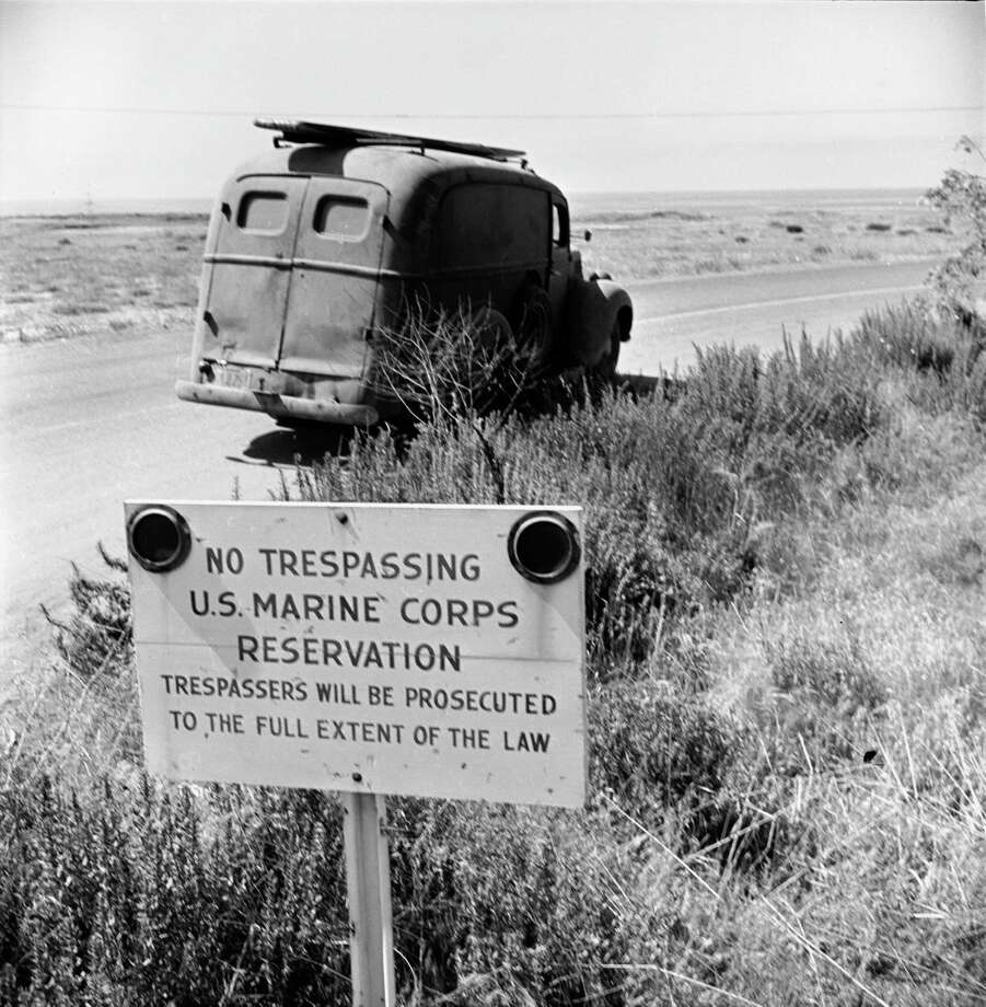 View of US Marine Corps sign that warns 'No Trespassing';  a van that belongs to surfers who ignore the sign is parked on the beach beyond, San Onofre, California, July 1950. Photo: Loomis Dean, File / Time & Life Pictures