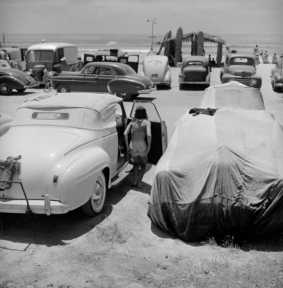 An unidentified woman changes into her bathing suit between cars parked at the beach, San Onofre, California, July 1950. Photo: Loomis Dean, File / Time & Life Pictures