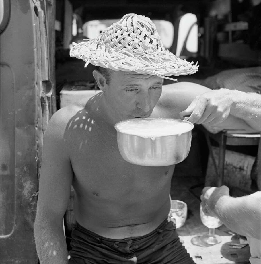 "American surfer Bob ""Hammerhead"" Gravage drinks a beer out of a sauce pan from a keg in his van as he hangs out at the beach with friends, San Onofre, California, July 1950. Photo: Loomis Dean, File / Time & Life Pictures"