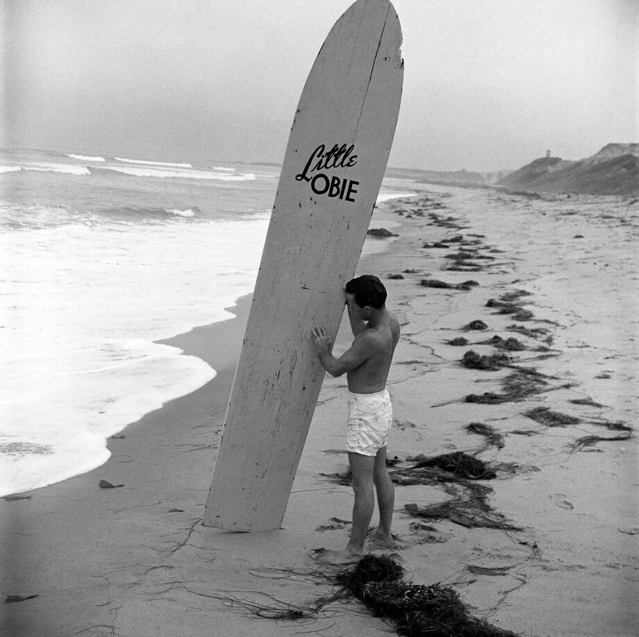 American surfer Obert Rod looks over his longboard, named 'Little Obie,' as he stands on a deserted beach, California, July 1950. Photo: Loomis Dean, File / Time & Life Pictures