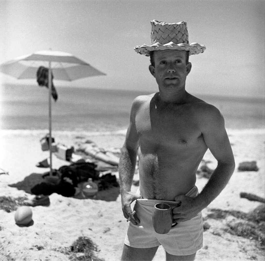 Portrait of American surfer Obert Rod as he stand on a beach, a cigatte in one hand and mug in the other, both of his thumbs hooked over the waistband of his swimming trunks, California, July 1950. Photo: Loomis Dean, File / Time & Life Pictures