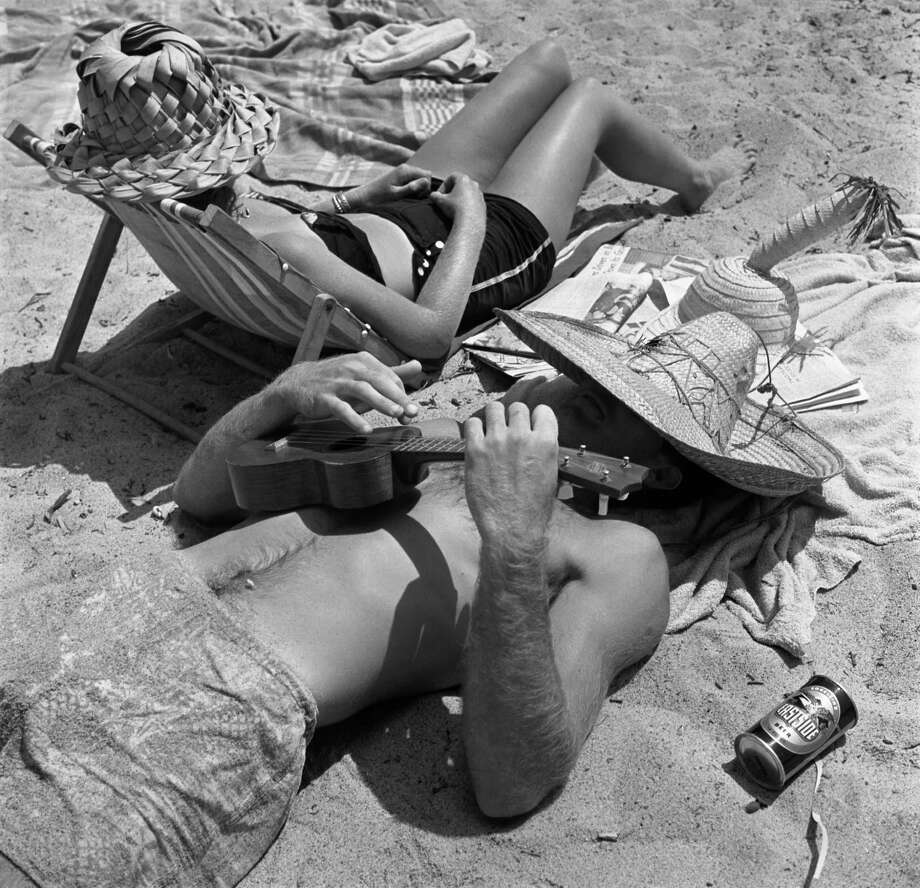 Facing opposite directions, an unidentified man and woman relax on the beach; both wear straw hats while the man plays a ukulele, California, July 1950. Photo: Loomis Dean, File / Time & Life Pictures