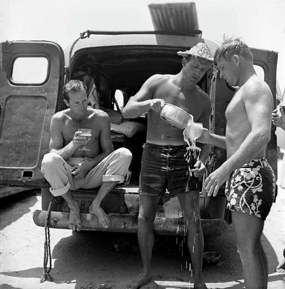 Surfer Hammerhead Gravage (C) pouring beer for friends from back of van where he lives. Photo: Loomis Dean, File / Time & Life Pictures