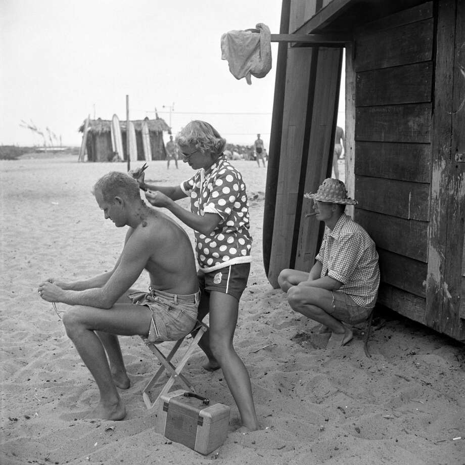Surfer Warren Miller getting his hair cut by friend Myra Roche. Photo: Loomis Dean, File / Time & Life Pictures