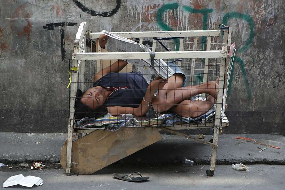 Just hanging in my crib, reading the newspaper: A Filipino catches up on current events along a street in downtown Manila. Photo: Aaron Favila, Associated Press