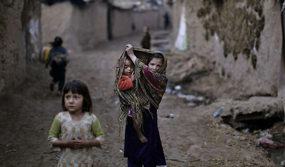 Afghanistan's displaced multitude:An Afghan refugee girl covers her sleeping sister with her head scarf while walking down an alley in a slum on the outskirts of Islamabad. Pakistan hosts more than 1.6 million registered Afghans, the largest and most protracted refugee population in the world, according to the United Nations. Photo: Muhammed Muheisen, Associated Press