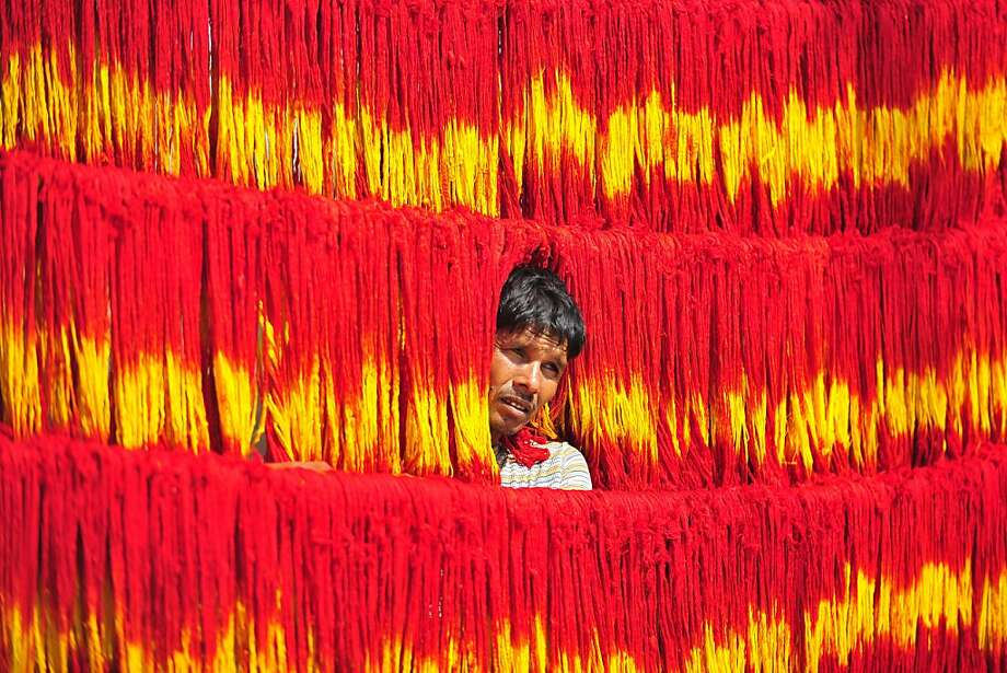 Primary colors: An Indian craftsman hangs freshly dyed kalawa, a sacred orange-yellow thread used in Hindu rituals, for drying at Lalgopalgunj village outside Allahabad. Photo: Sanjay Kanojia, AFP/Getty Images