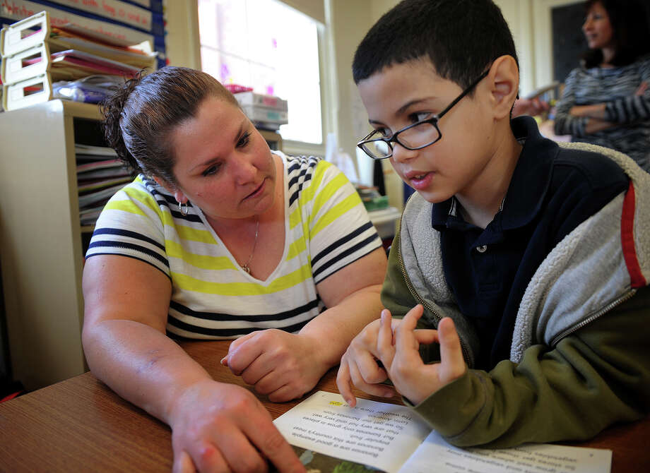 Teacher Tara Oliwa works on reading with second grader Yahir Casiano in her class, a blend of autistic, and non-autistice students, at Beardsley School in Bridgeport, Conn. on Wednesday, April 10, 2013. Photo: Brian A. Pounds / Connecticut Post