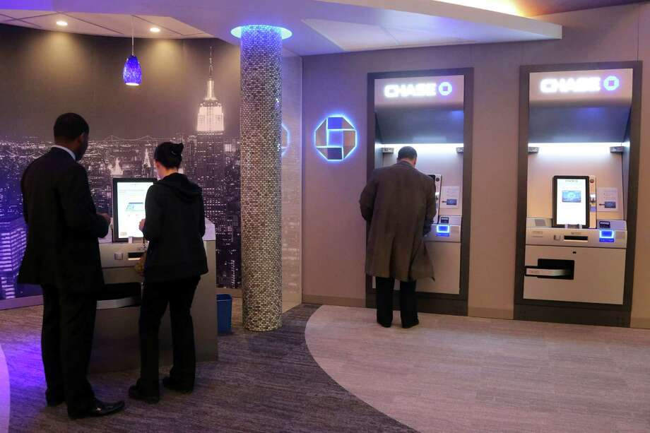 """In this Friday, March 1 2013 photo, people use the Self Service Banking Kiosks at a JPMorgan Chase lobby in New York.  JPMorgan Chase executives  are touting what they call their """"Branch of the Future,"""" a place where ATMs distribute exact change, machines count cash so tellers don't have to. (AP Photo/Mary Altaffer) Photo: Mary Altaffer"""