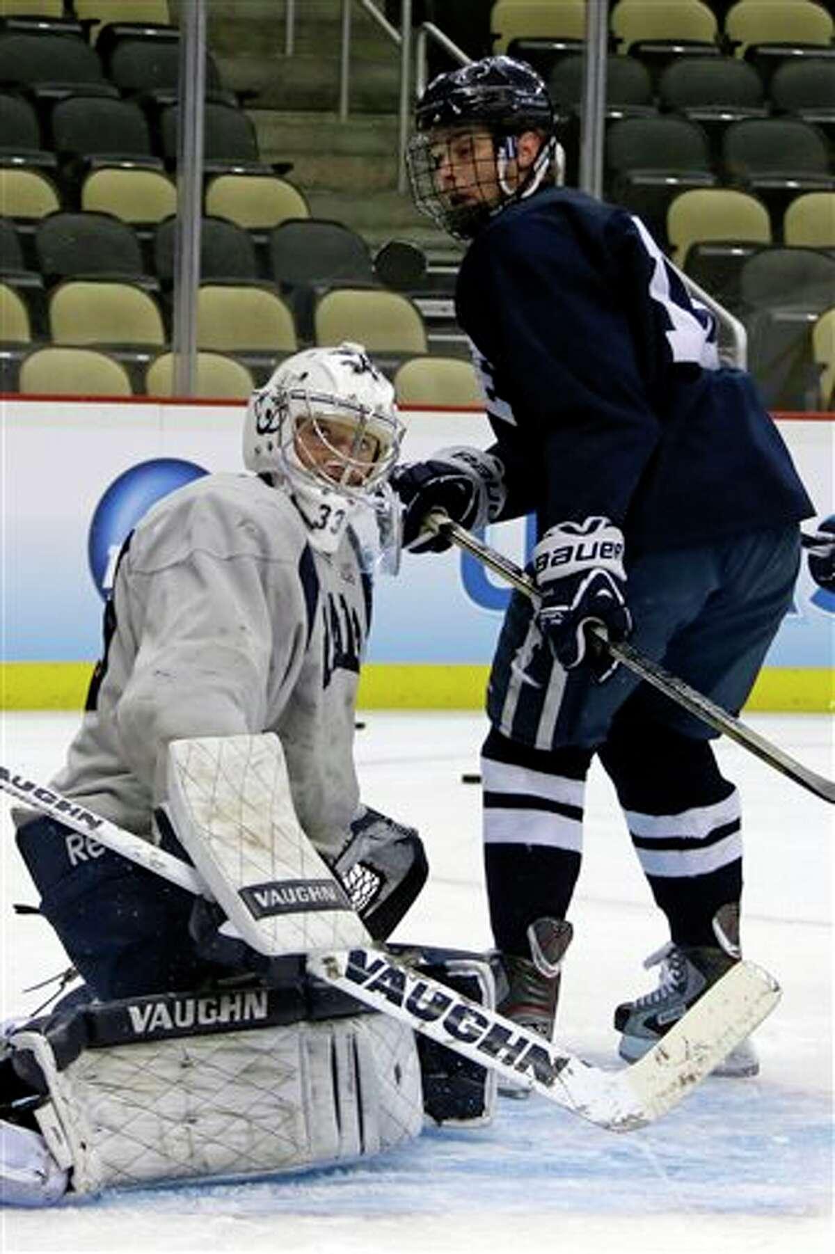 Yale goalie Jeff Malcolm, left, blocks a shot by teammate Clinton Bourbonais during an NCAA college hockey practice in Pittsburgh, Wednesday, April 10, 2013. (AP Photo/Gene J. Puskar)
