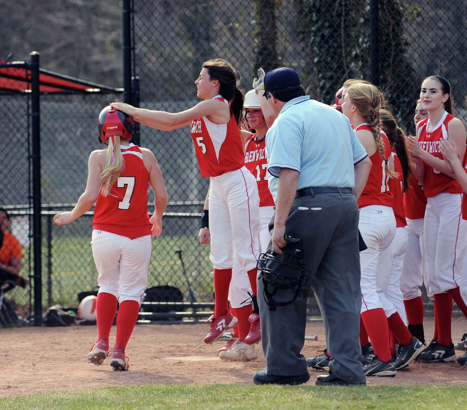At left, Rebecca DeCarlo # 7 of Greenwich is congratulated by Jennifer Ambrogio # 5 and her teammates after hitting a homerun to lead off the game for Greenwich in the bottom of the first inning during the girls high school softball game between Greenwich High School and Stamford High School at Greenwich, Wednesday, April 10, 2013. Greenwich won the game 7-5 to remain unbeaten. Photo: Bob Luckey / Greenwich Time