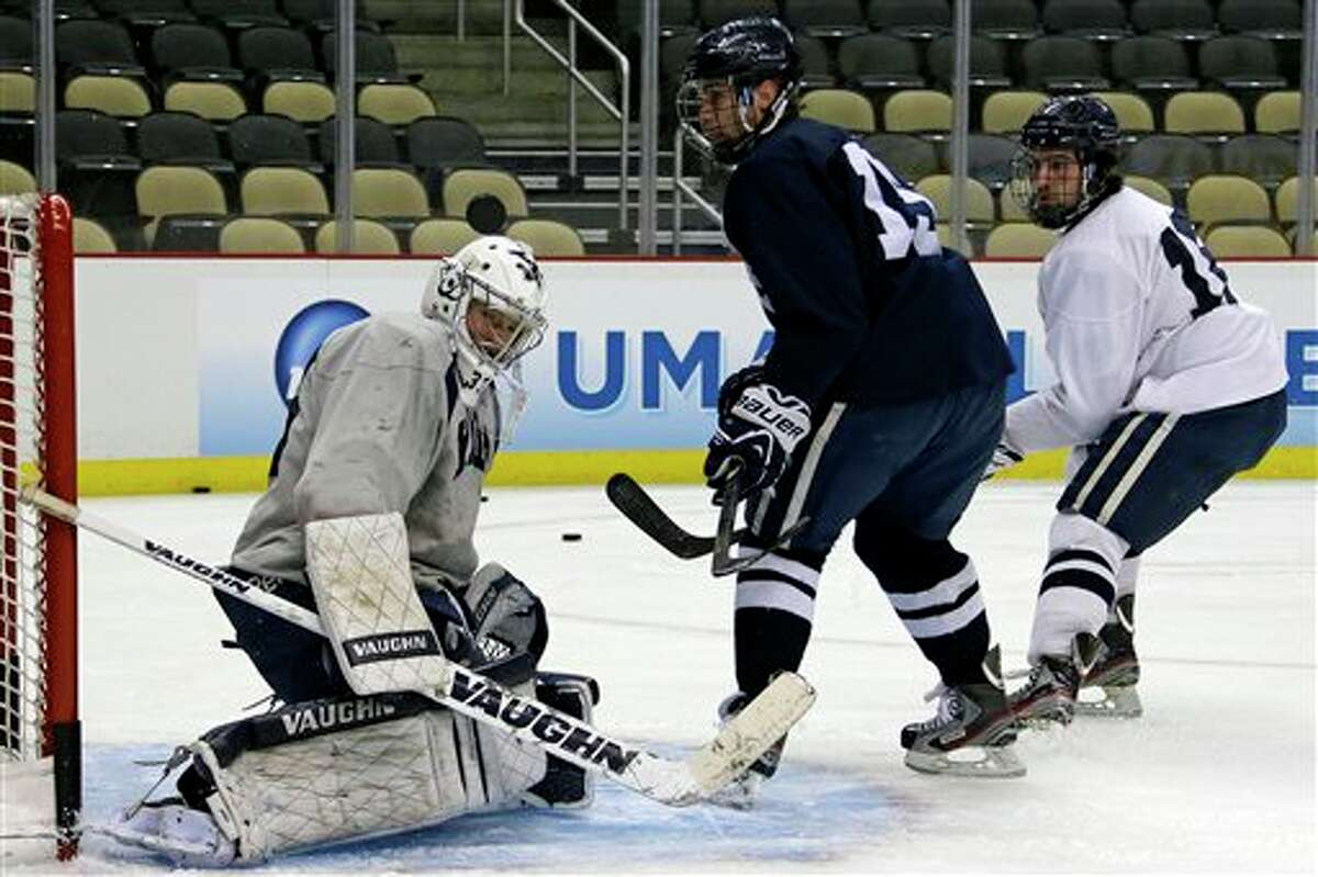 Yale goalie Jeff Malcolm, left, blocks a shot by Clinton Bourbonais, center, with Mitch Witek on defense during an NCAA college hockey practice in Pittsburgh, Wednesday, April 10, 2013. (AP Photo/Gene J. Puskar)