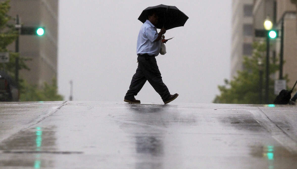 A man tries to stay dry while crossing the street at Franklin and Travis as a rainy cold front hits Houston.