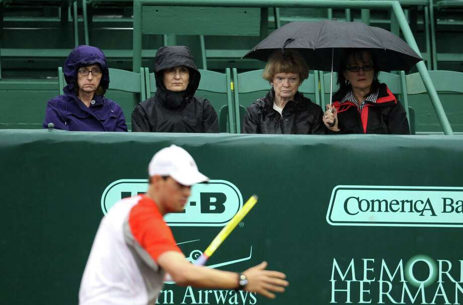 Spectators try to stay dry during a slight drizzle, moments before a rain delay was called during the doubles match between Bob and Mike Bryan and  Oliver Marach and Andre Sa, during the first round of the US Men's Clay Court Championships, Wednesday, April 10, 2013, in Houston. Photo: Karen Warren, Houston Chronicle / © 2013 Houston Chronicle