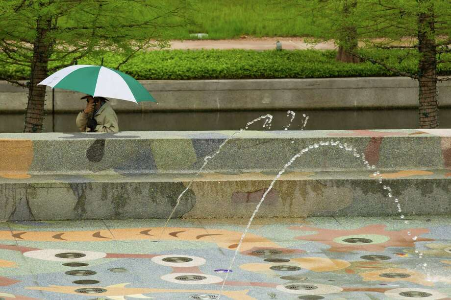 A man walks past a fountain under an umbrella as mist falls near The Woodlands Waterway Wednesday, April 10, 2013, in The Woodlands. Photo: Brett Coomer, Houston Chronicle / © 2013 Houston Chronicle