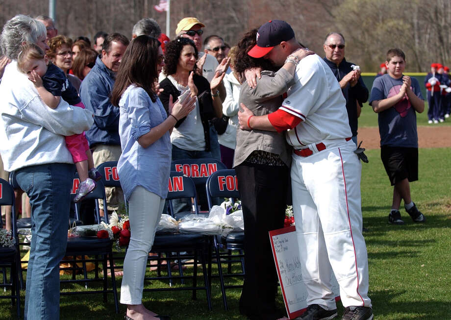 Foran High baseball coach Garret Walker, son of the late former coach Ken Walker, hugs his mother Nancy Walker, during a ceremony to rename Foran High's baseball field in honor of his father, which was held before Wednesday's game against Jonathan Law in Milford, Conn. on Wednesday April 10, 2013. At left is Ken's daughter Whitney, and sister JoAnne Walker, with grandaughter Delaney, 2. Photo: Christian Abraham / Connecticut Post