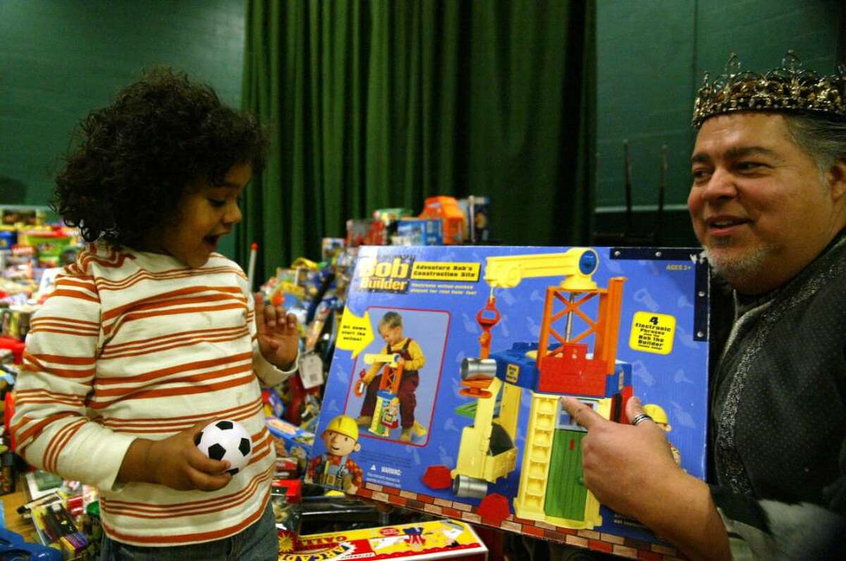 Eddie Christopher Moro, 3, reacts as he gets a Bob the Builder toy from, retired Bridgeport Firefighter, Ron Morales during the Three Kings celebration at Luis Munoz Marin School in Bridgeport. Wednesday, Jan. 6, 2009.