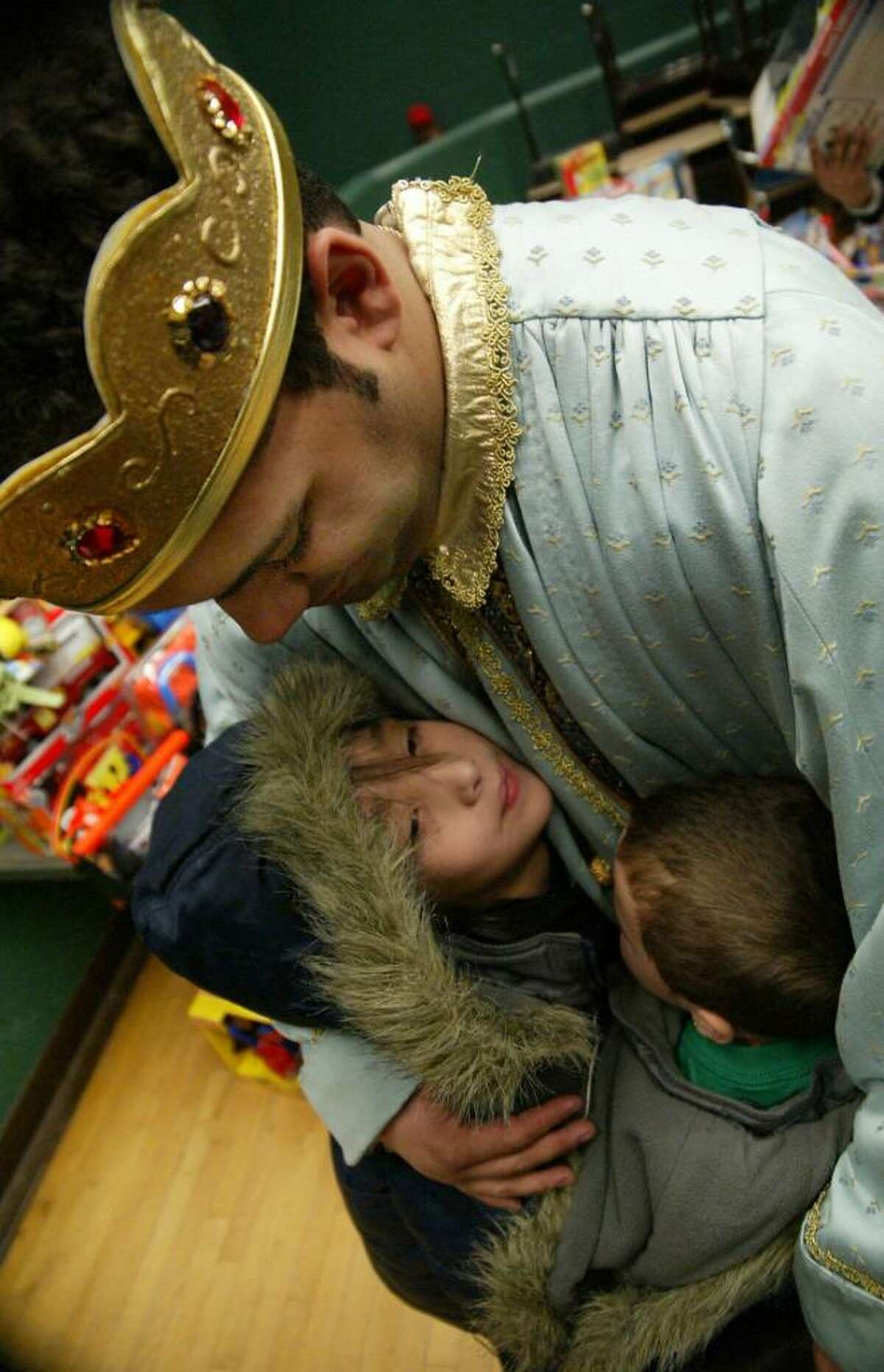 Bridgeport firefighter, Christopher Vega gets a hug from brothers (L-R) Jacob, 7, and Dustin Bonilla, 3, during the Three Kings celebration at Luis Munoz Marin School in Bridgeport. Weednesday, Jan. 6, 2010.