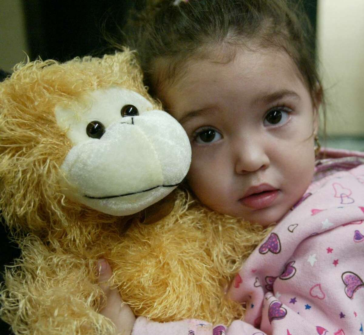 Aliana Adorno, 1, hugs her new monkey during the Three Kings celebration at Luis Munoz Marin School in Bridgeport, Wednesday, Jan. 6, 2009.