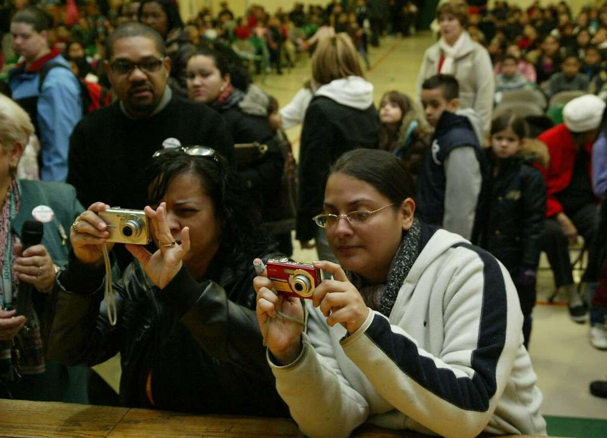 (L-R) Yvette Gonzales and Veronica Pagan take pictures during the annual Three Kings celebration at Luis Munoz Marin school in Bridgeport. Wednesday, Jan. 6, 2009.