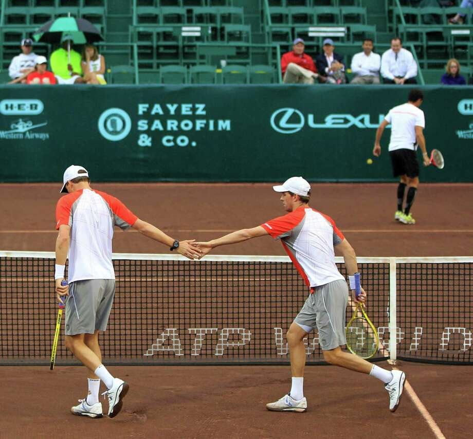 Bob, left, and Mike Bryan, right, high-five each other as they play doubles against Oliver Marach and Andre Sa, during the first round of the US Men's Clay Court Championships, Wednesday, April 10, 2013, in Houston. Photo: Karen Warren, Houston Chronicle / © 2013 Houston Chronicle