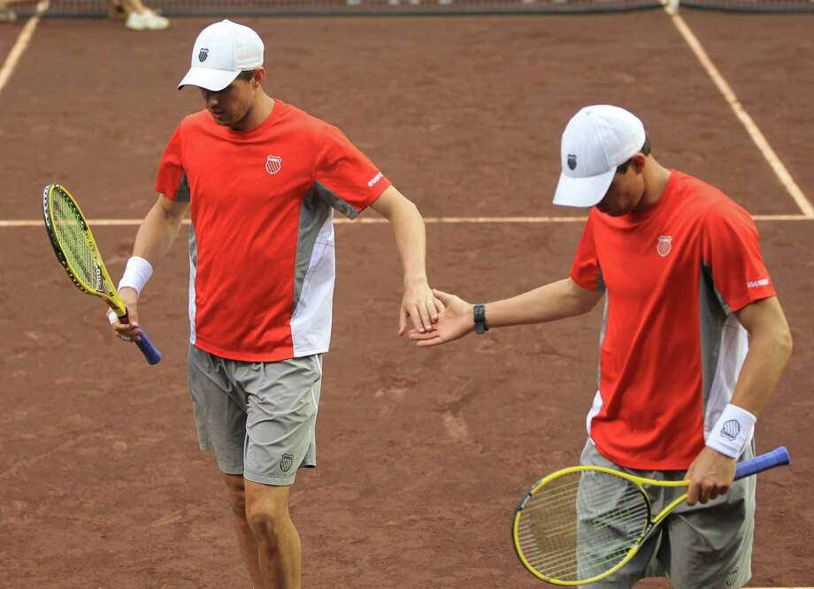 Mike, left, and Bob Bryan high-five each other as they play doubles against Oliver Marach and Andre Sa, during the first round of the US Men's Clay Court Championships, Wednesday, April 10, 2013, in Houston. Photo: Karen Warren, Houston Chronicle / © 2013 Houston Chronicle